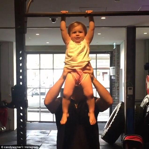 Ivy Mae Warner performs pull ups with a little help from